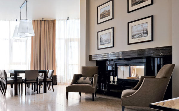 Stylish white and beige living room with two brown armchairs either side of a wide black fireplace
