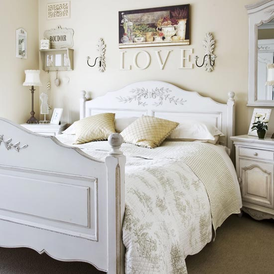 White and cream bedroom with the word love above the white wooden bed