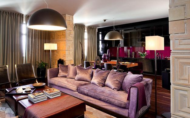 Purple Sofa With Dining Table And Black And Purple Kitchen Behind It