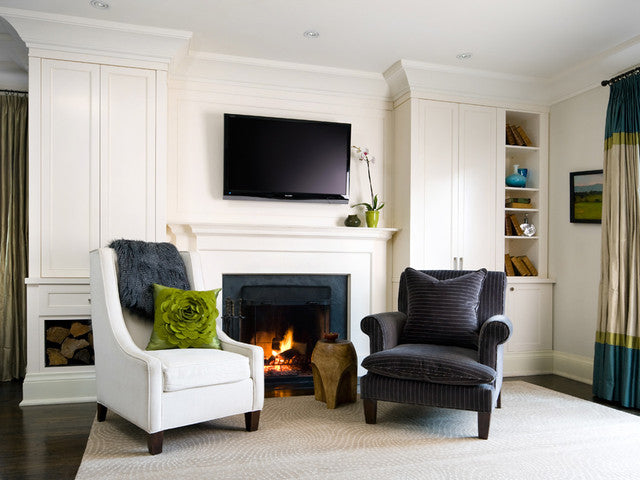 White living room with one white and one white armchair either side of a roaring fireplace