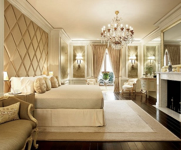 Cream and beige luxury bedroom with beige padded diamond shaped wall panels and a ceiling chandelier