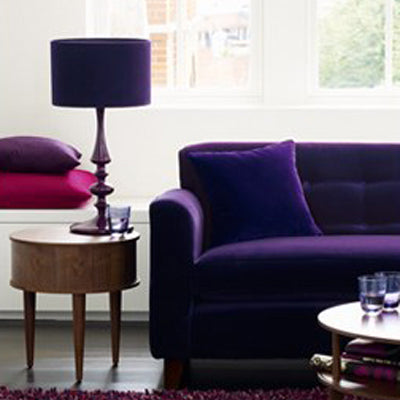 Purple Sofa Next To A Matching Lamp, In Front Of A Large Window