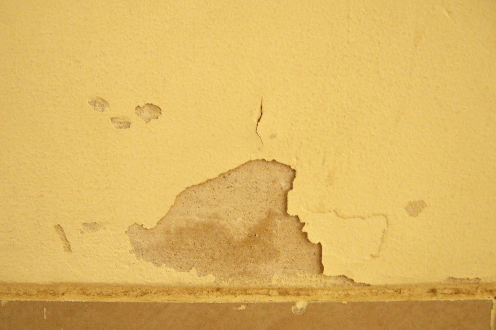 Yellow paint peeling off a wall