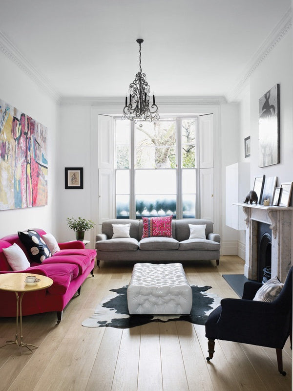 White living room with hardwood floors, one pink sofa and one grey sofa