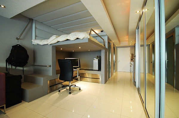 Grey and cream modern living space with loft bed above an office desk and mirrored storage