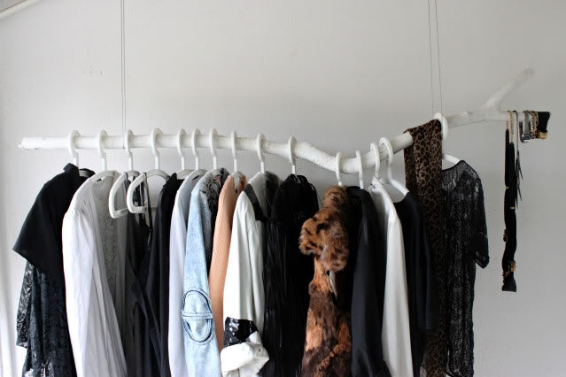 White branch clothes rail hung from the ceiling using string