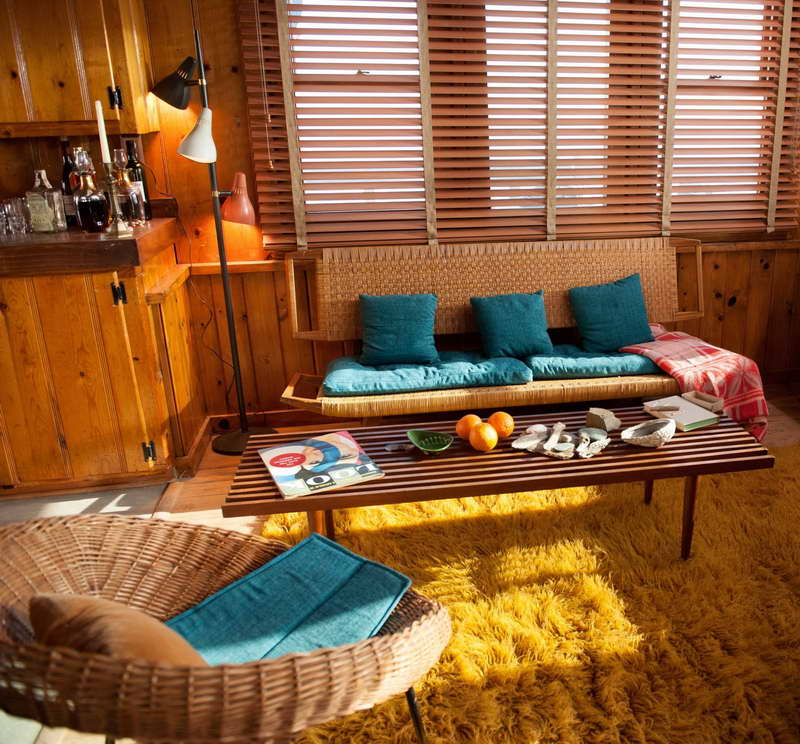 1960s style living room and kitchen with lots of wooden panels, yellow rug and teal seat pads and cushions on rattan chairs
