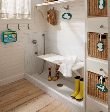 Cream mud room with white bench for washing shoes and wellies