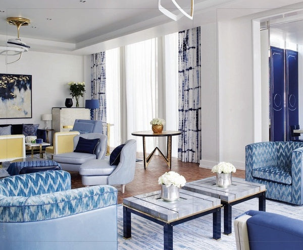 White and blue living room with tie dye on the curtains and chairs