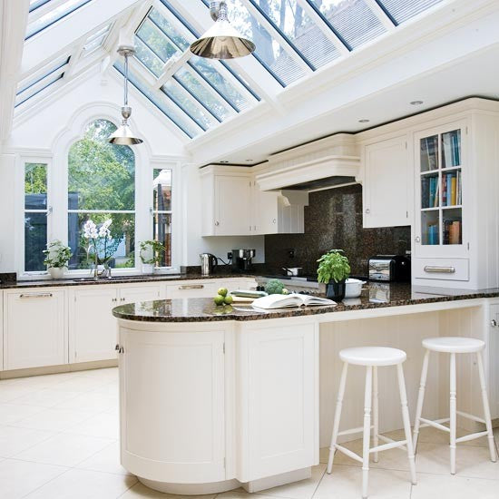 White kitchen with dark worktops and a glass pitched roof