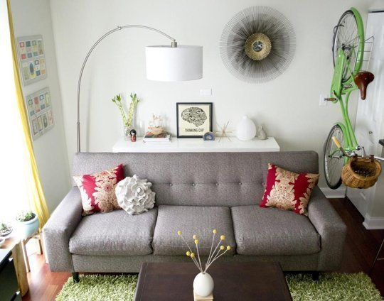 Grey Sofa, White Room And Green Bike Suspended To The Right Of The Sofa