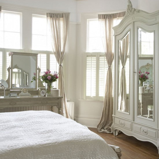 Cream, white and beige bedroom with mirror wardrobe at the end of the bed