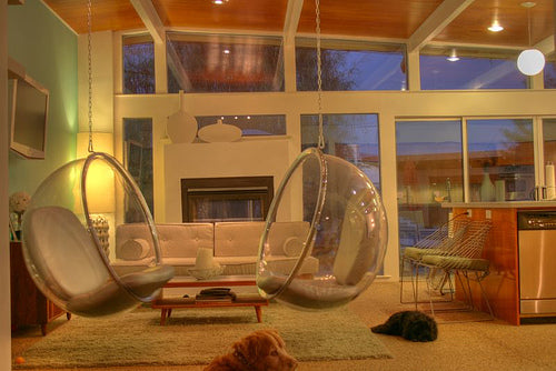 60s style glass pod chairs suspended from the ceiling in a living room
