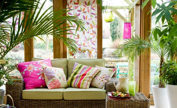 Wood and glass conservatory with pink, green and orange fabric
