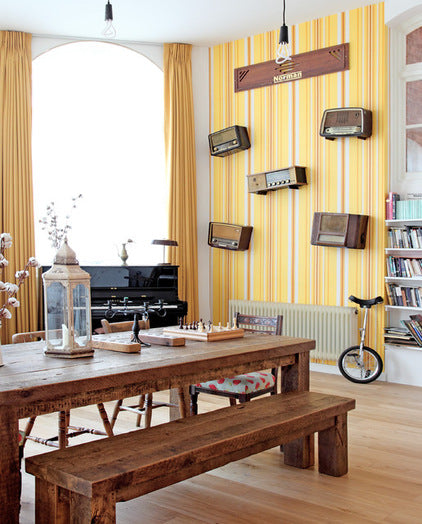Yellow Eclectic Dining Room With Wooden Furniture And Old Radios Hung On The Wall