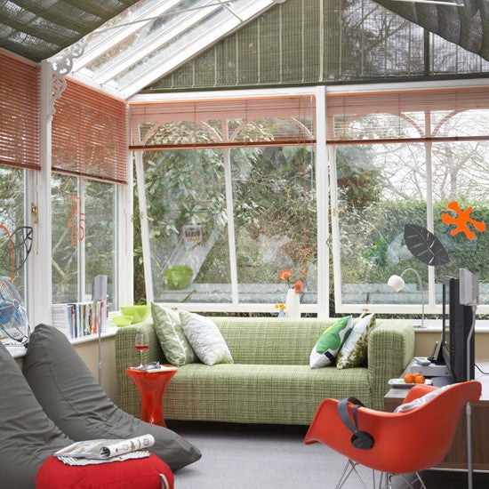 White conservatory with red and grey blinds, and light green sofa and grey bean bags