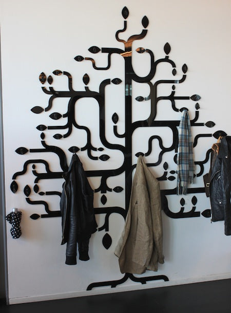 Funky weaving black tree branches on a white wall with hooks on each branch to hang coats