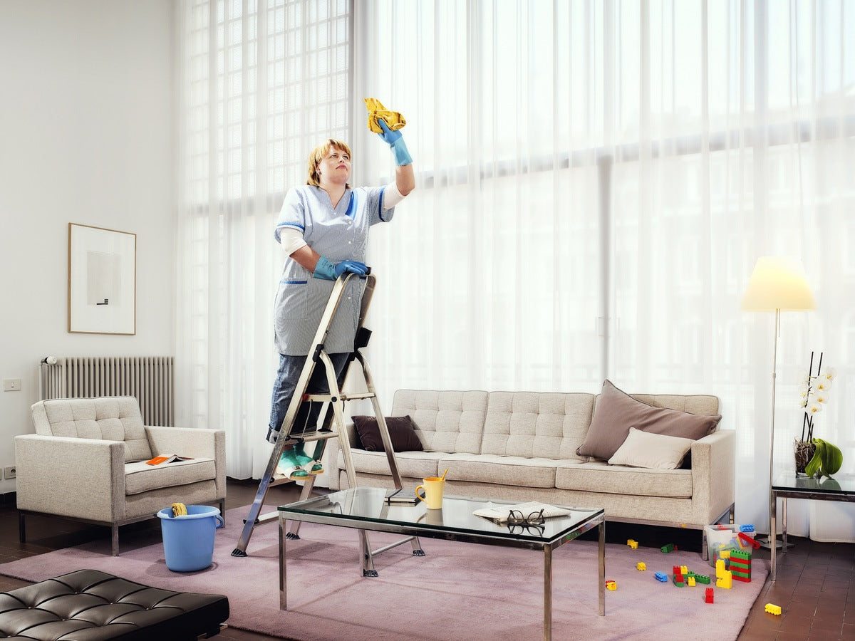 Cleaning lady in large high ceiling living room