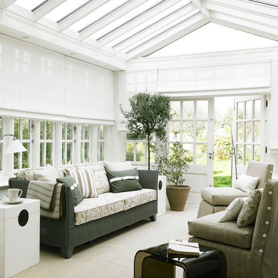 White conservatory with potted plants, sofa and arm chairs