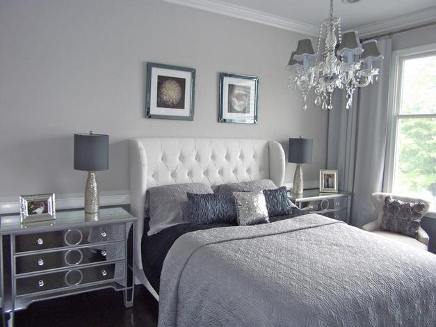 Light grey and white bedroom, with mirror covered drawers by the side of the bed