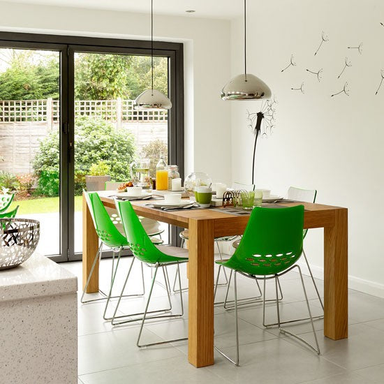 Fresh white kitchen dining room with wooden table and green and white plastic chairs