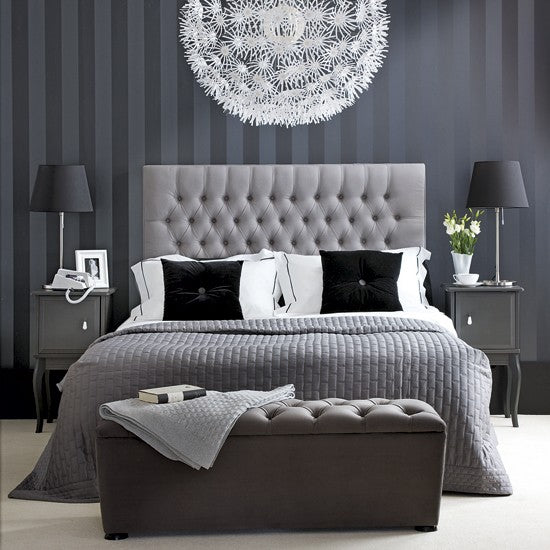 Black and dark grey bedroom with double bed and striped black wallpaper