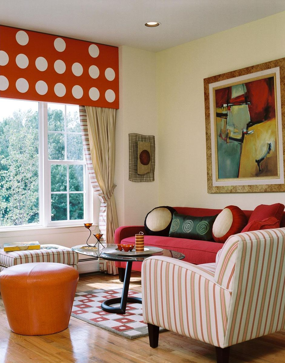 Cream living room with red blinds and sofa, orange footstool, glass table and orange and white striped armchair