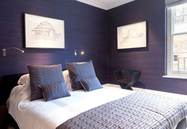 Indigo and white bedroom with pencil drawings on the walls of buildings and structures