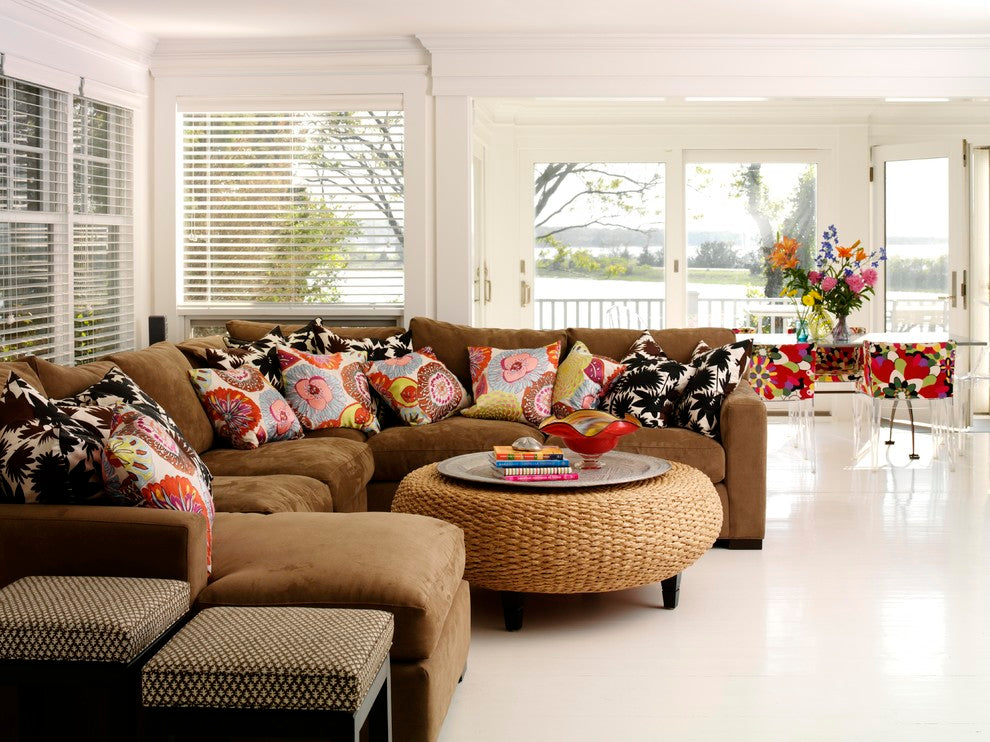 Round ottoman coffee table and dark brown suede corner sofa in a large white room
