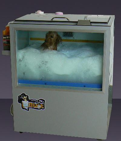 A dog washing machine with a glass side where you can see a dog get washed, covered in suds