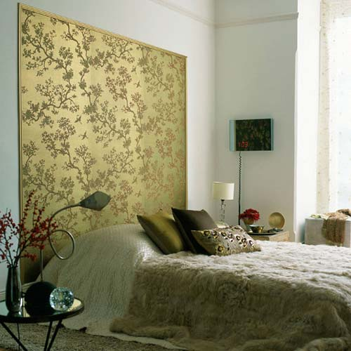 Gold wallpaper headboard with an intricate floral pattern