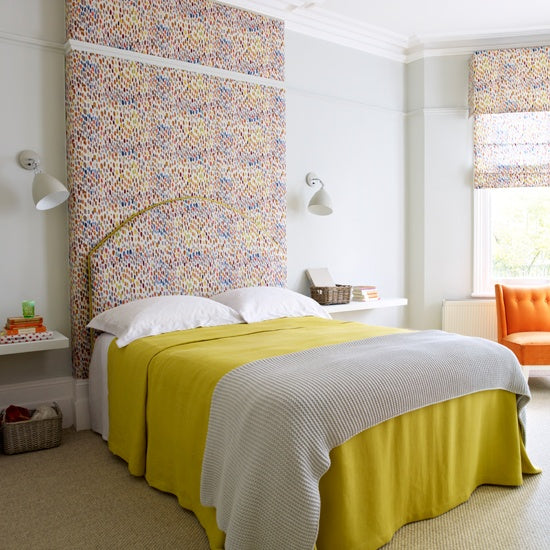 White bedroom, yellow bedding and speckled multi colour headboard