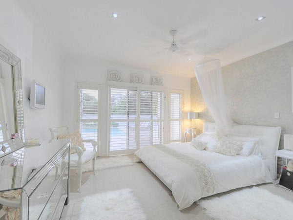 All white bedroom with shutters on the doors, leading out to a pool