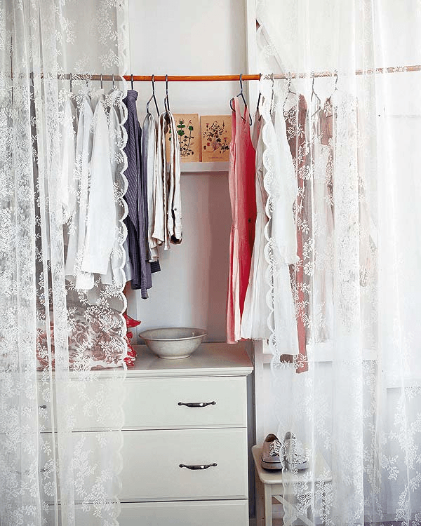 Wooden bamboo clothes rail above white drawers, and behind a white voile