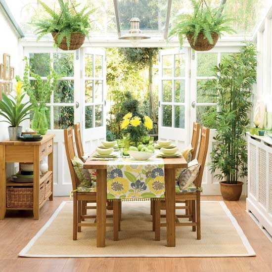 Bright and fresh white conservatory with dining table and green tablecloths