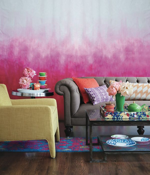 Pink and white paint dipped effect on a wall behind and grey sofa and yellow armchair