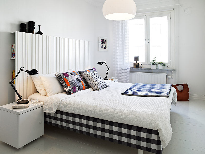 White bedroom with double bed, white bedding and grey, orange and purple cushions