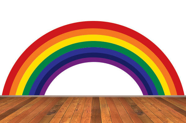 A rainbow on a white wall, with wooden flooring