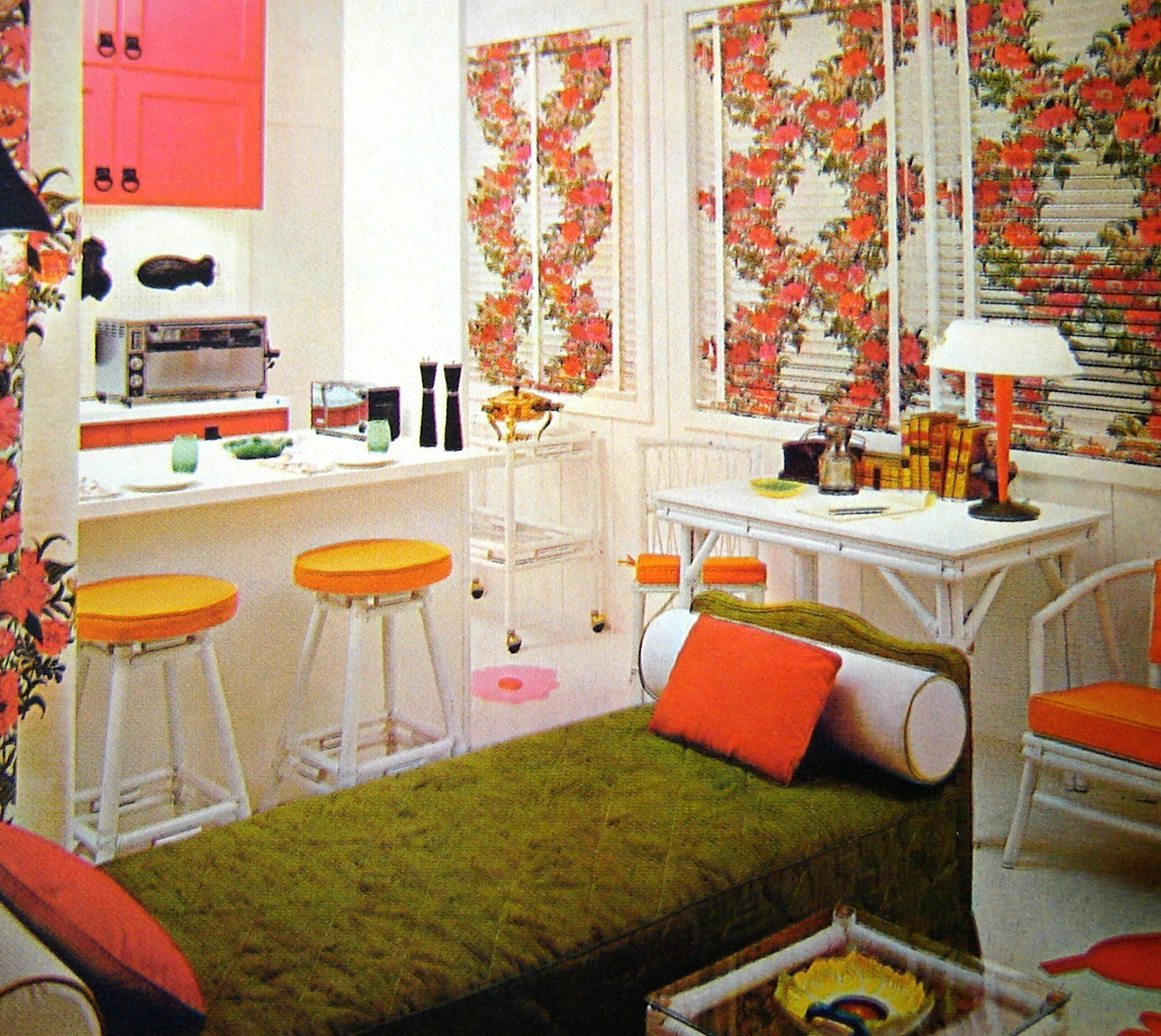 Old fashioned sixties kitchen and living area with Chintz floral patterns in white and orange throughout