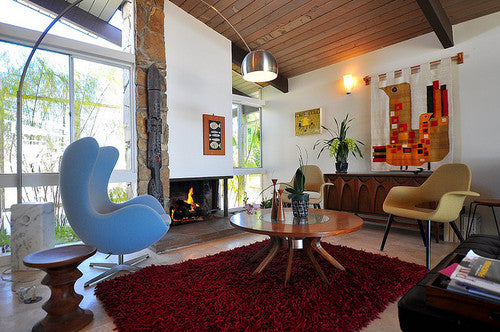 Sixties style living room with large blue swivel chair and red rug