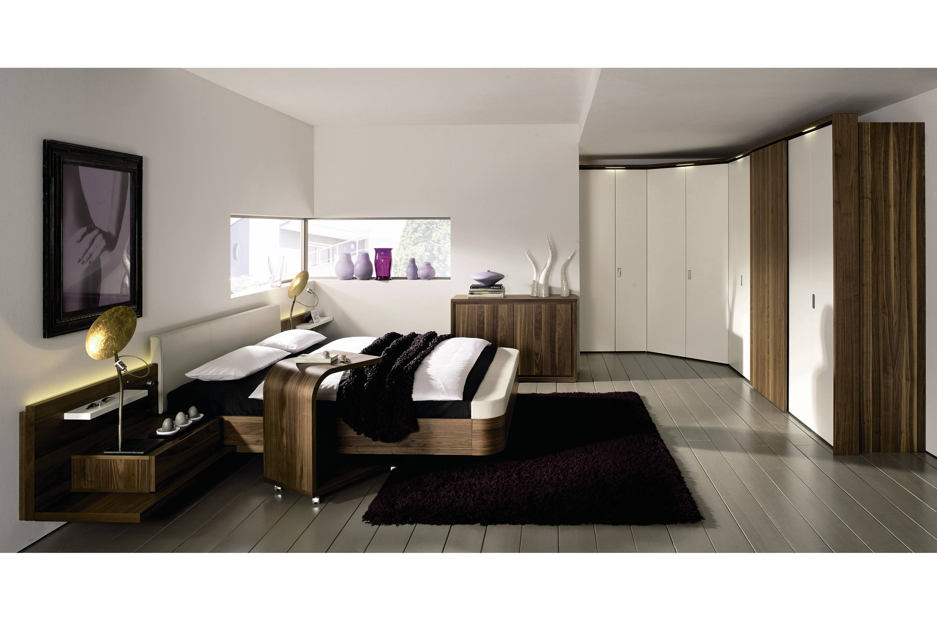 Wooden floor, cream walls, dark wood bed and wide fitted wardrobes