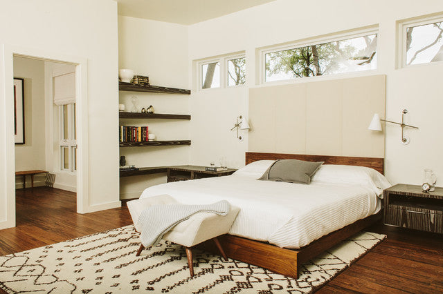 Modern white bedroom with stained wood bed frame and white bedding