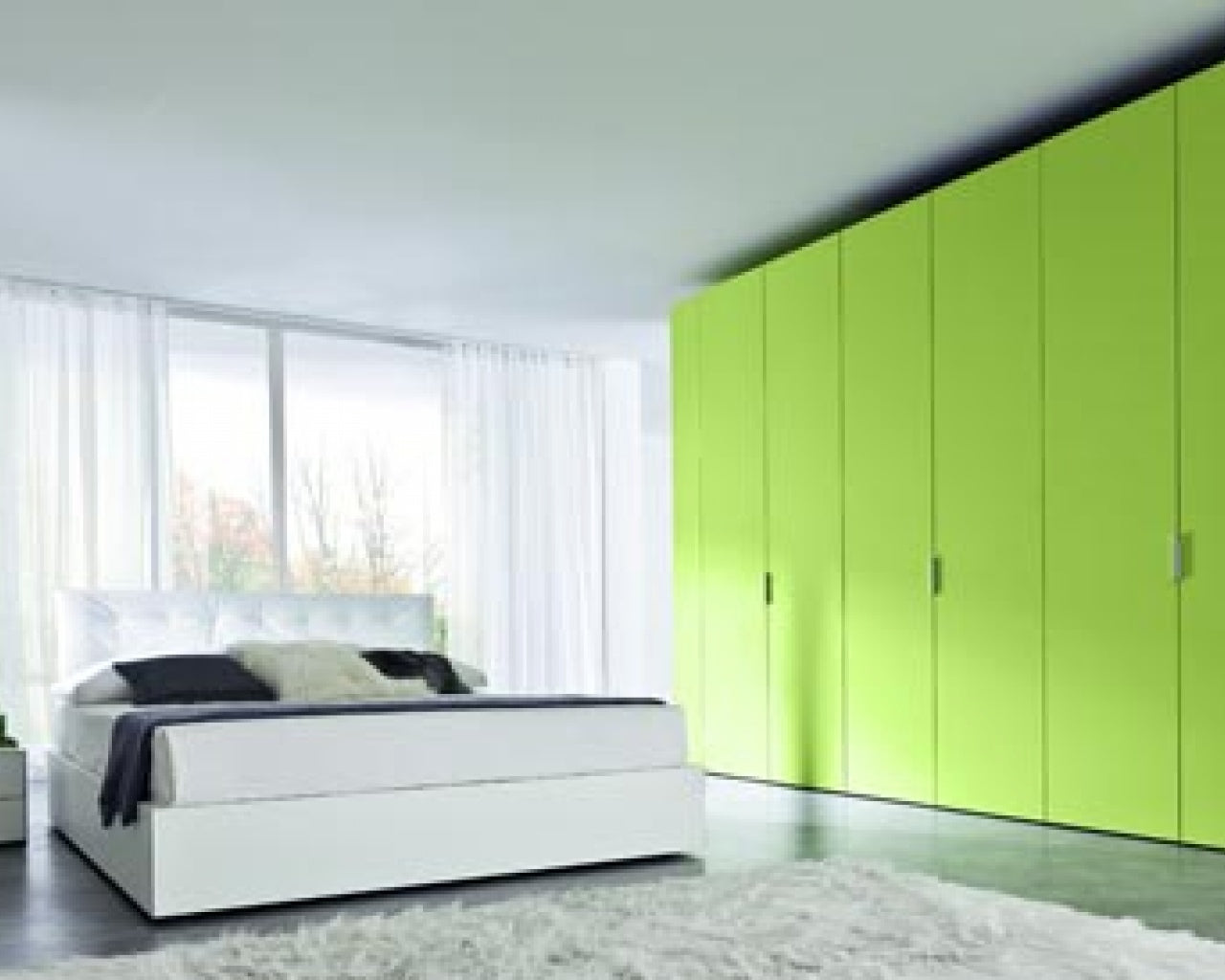Modern, white and fresh bedroom with full wall of light green wardrobes