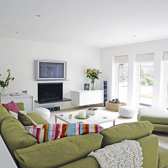 Bright modern white living room with large green corner sofa