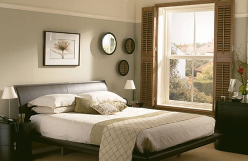 Cream and light grey bedroom with wooden shutters at the window