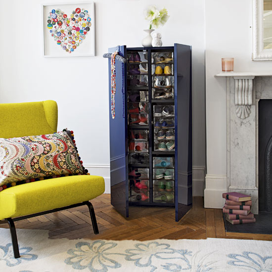 Dark blue shoe storage unit, between a yellow arm chair and a white fireplace