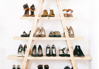A natural wood A-frame of shelves, with shoes laid out on each shelf