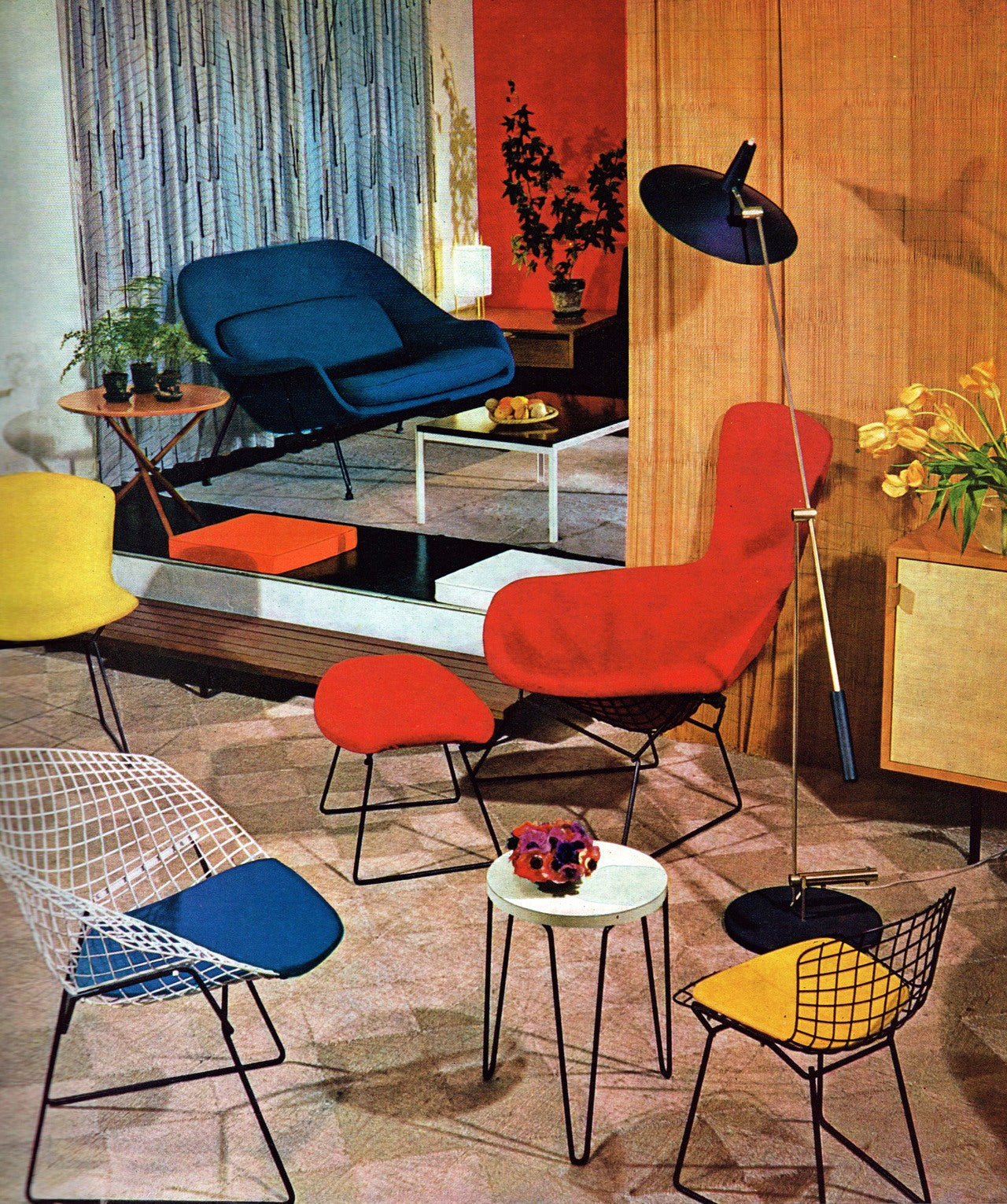Period photograph of a sixties living room with bright red, yellow and blue metal chairs