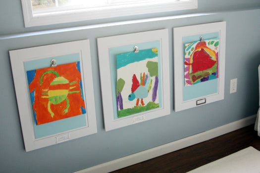 Three painting by a child positioned under a window-