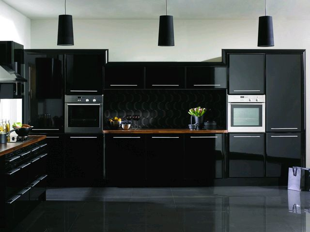 Reflective black kitchen units, black floor tiles and white walls above the units
